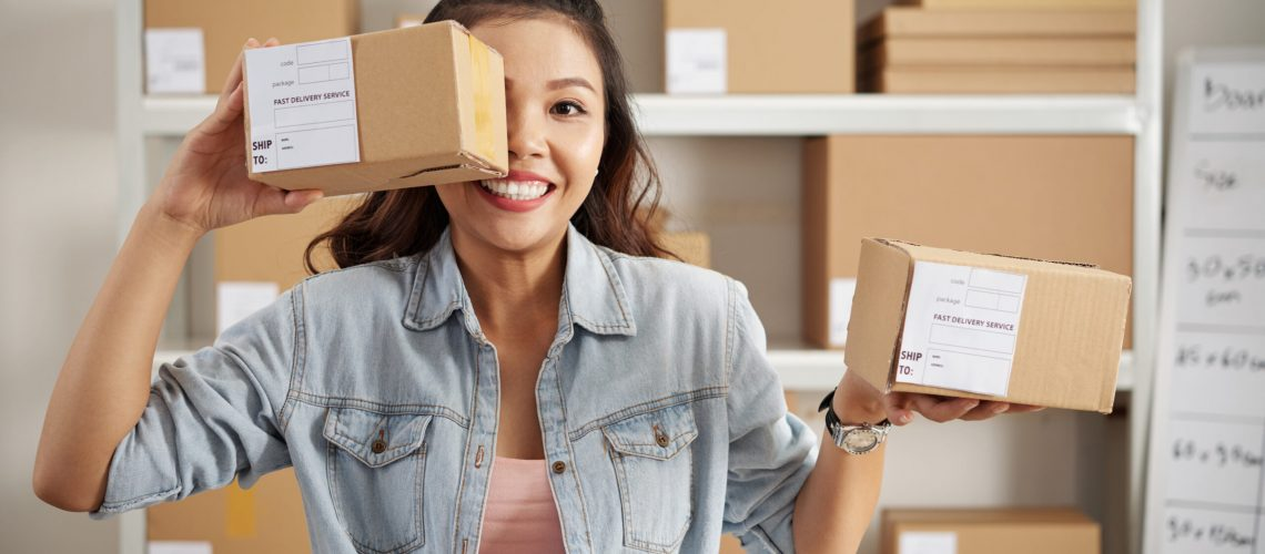Happy Asian woman holding small packed parcels for customers, she is at storehouse